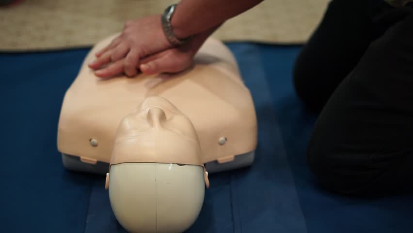 Cardiopulmonary Resuscitation (CPR) Training Demonstrating Chest Compression On A Dummy Royalty-Free Stock Footage #1008657682
