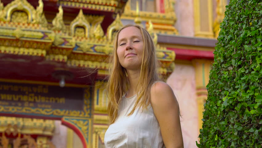 Young woman visiting a Wat Chalong temple on Phuket island, Thailand