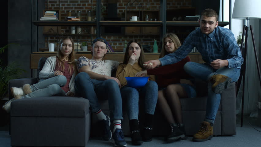 Group of cheerful teenage friends watching comedy movie on TV with popcorn and laughing while sitting on sofa at home. Excited casual friends relaxing and watching television in living room. | Shutterstock HD Video #1008668848