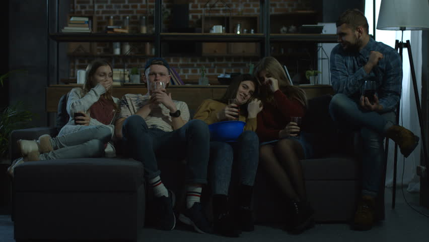 Group of teenage best friends watching horror movie with popcorn at home in the evening while sitting comfortable on sofa. Young hipster teenagers relaxing and watching tv in domestic room. | Shutterstock HD Video #1008668851