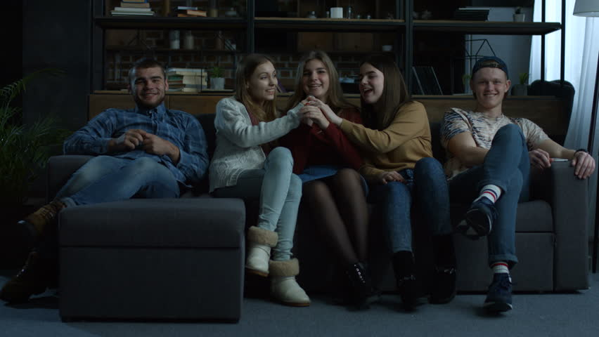 Portrait of joyous guys and girls with microphone singing karaoke together while sitting on the couch in domestic interior. Group of carefree young friends performing song sa they relaingx at home. | Shutterstock HD Video #1008668854