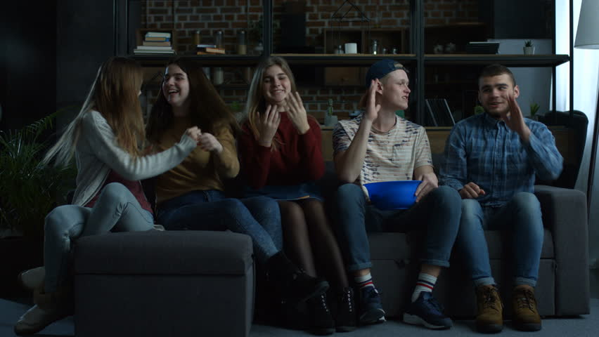 Happy football fans watching soccer on tv, cheerng for team and celebrating victory while sitting on the couch with popcorn in domestic room. Group of excited friends watch sport on television at home | Shutterstock HD Video #1008668875