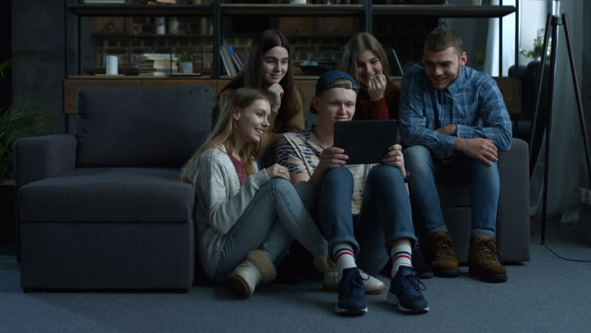 Group of cheerful young friends grouped around tablet computer and watching media content as they sit together in domestic room. Joyful hipster teenagers using digital tablet pc at home. | Shutterstock HD Video #1008668890