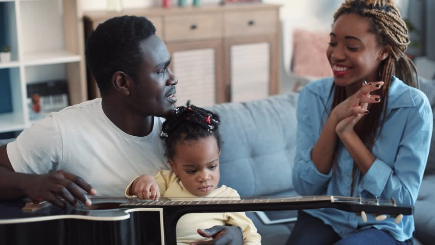 Happy family playing on guitar and singing, clapping their hands, spending time together while sitting on the sofa in a cozy living room. Slow motion | Shutterstock HD Video #1008692992