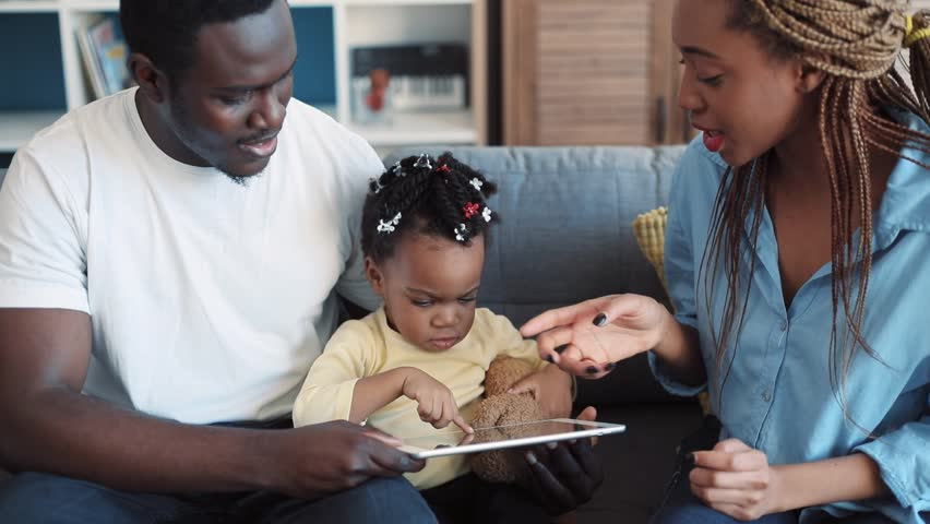 Adorable little baby-girl surrounded by her parents slides the touch screen of the tablet with her finger, her mother claps her hands. Cheerful mood, positive emotions. Family time. Slow motion | Shutterstock HD Video #1008693154