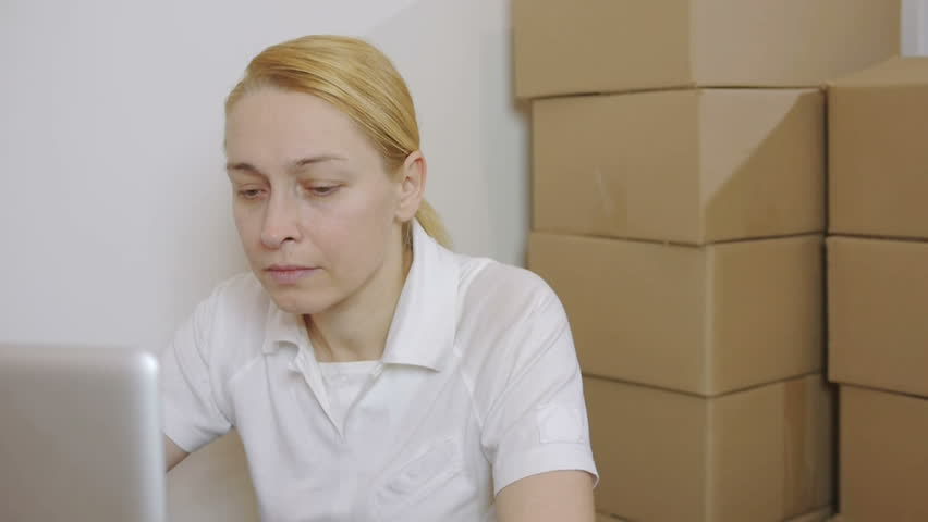 Woman using a laptop sitting on the floor in a room with cardboard boxes | Shutterstock HD Video #1008694360