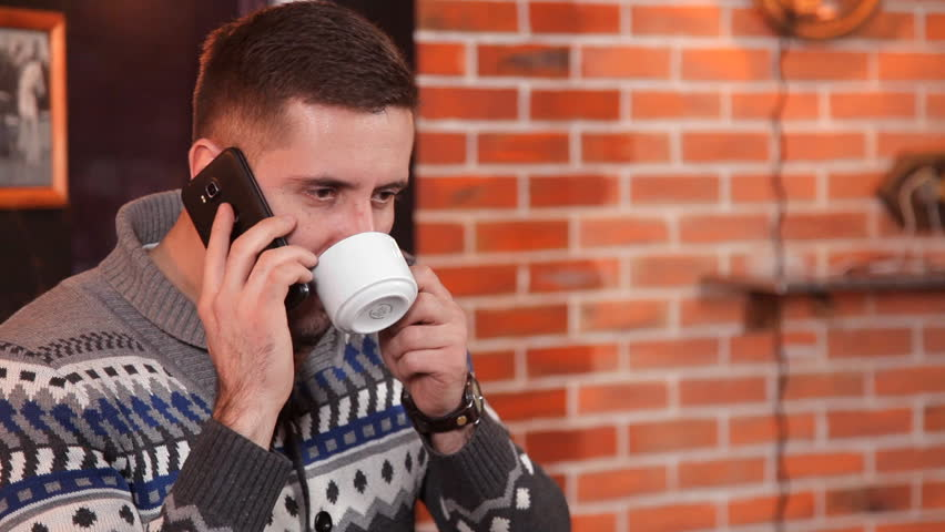 An attractive young man in a restaurant drinking coffee and talking on a mobile phone | Shutterstock HD Video #1008695575