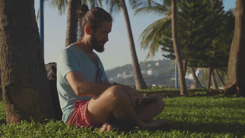 Man in nature park sitting with laptop under a palm tree. Freelancer open laptop and start work in slow motion | Shutterstock HD Video #1008700453
