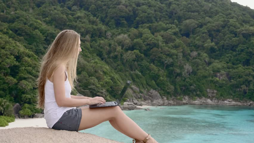 Business woman using laptop computer on top of the mountain with a view over white sand beach. Vacation, freelance job, leisure activity concept. | Shutterstock HD Video #1008703417