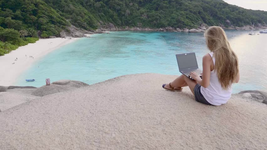 Business woman using laptop computer on top of the mountain with a view over white sand beach. Vacation, freelance job, leisure activity concept. | Shutterstock HD Video #1008703423