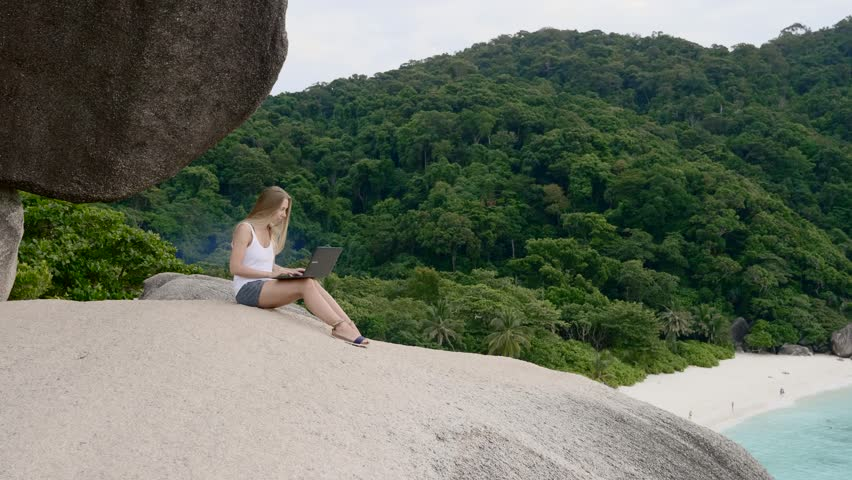 Business woman using laptop computer on top of the mountain with a view over white sand beach. Vacation, freelance job, leisure activity concept. | Shutterstock HD Video #1008703426