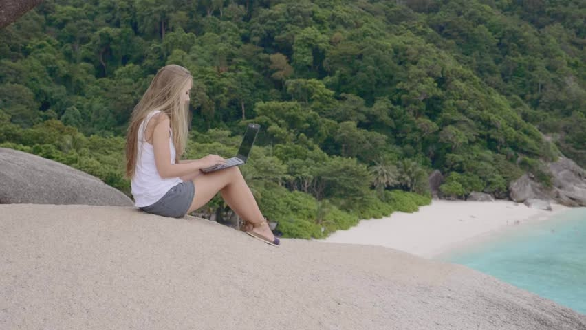 Tourist woman on holidays enjoying online with a laptop on top of the mountain with view over white sand beach with turquoise sea and tropical rainforest background. Vacation,recreation and freelance | Shutterstock HD Video #1008703471