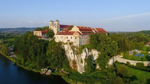 Tyniec near  Krakow, Poland.  Benedictine abbey on the rocky hill and cliff at Vistula River. Aerial flyby 4K video in sunset light