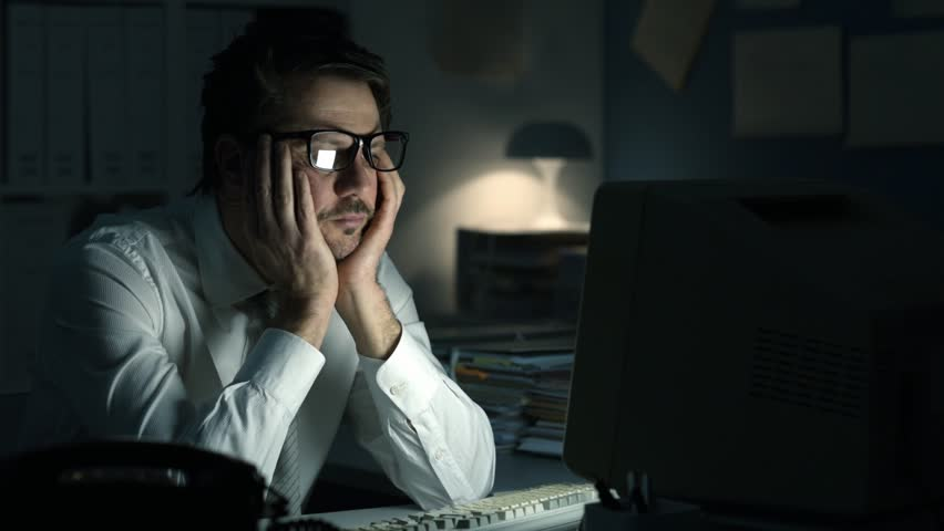 Tired frustrated business executive working late at night in the office, he is sitting at desk, staring at the computer screen and waiting | Shutterstock HD Video #1008714344
