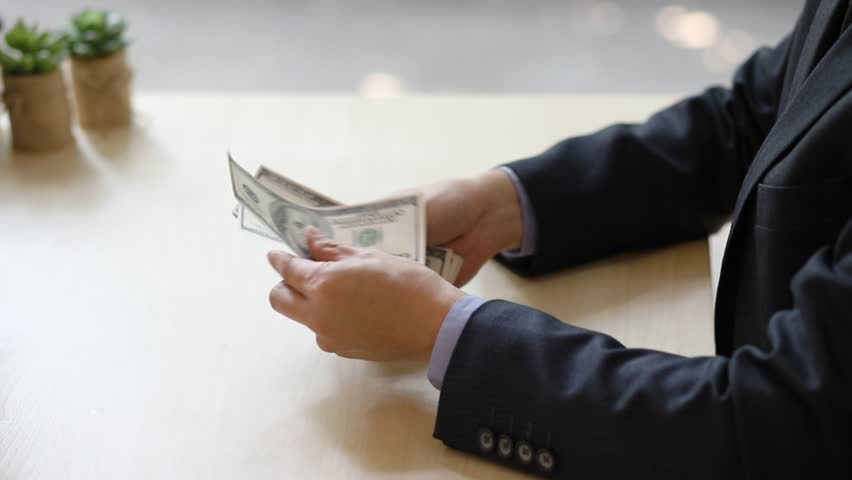 Closeup of a businessman, Bank employee hands counting hundred dollar bills at a table, Business, Financial, Banking, Exchange concept. | Shutterstock HD Video #1008716819