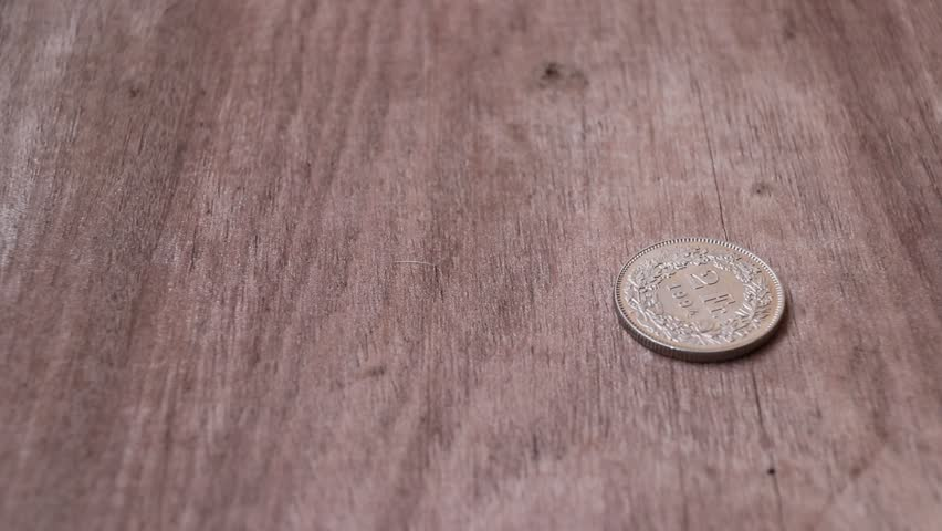 Spin of 2 Swiss Franc of Switzerland money on the wooden floor and stop in reverse of a coin with 1994. The concept of finance. | Shutterstock HD Video #1008716888