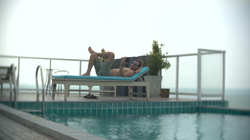 A young man with a tablet at the pool on the roof overlooking the sea. 4k. , blur the background | Shutterstock HD Video #1008723257
