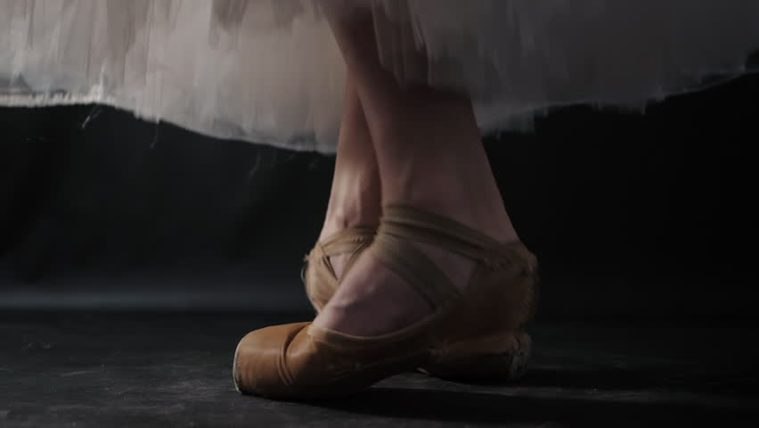 Close up of ballet dancer as she practices exercises on dark stage or studio. Woman's feet in pointe shoes. Ballerina shows classic ballet pas. Slow motion. Flare, gimbal shot. #1008724079