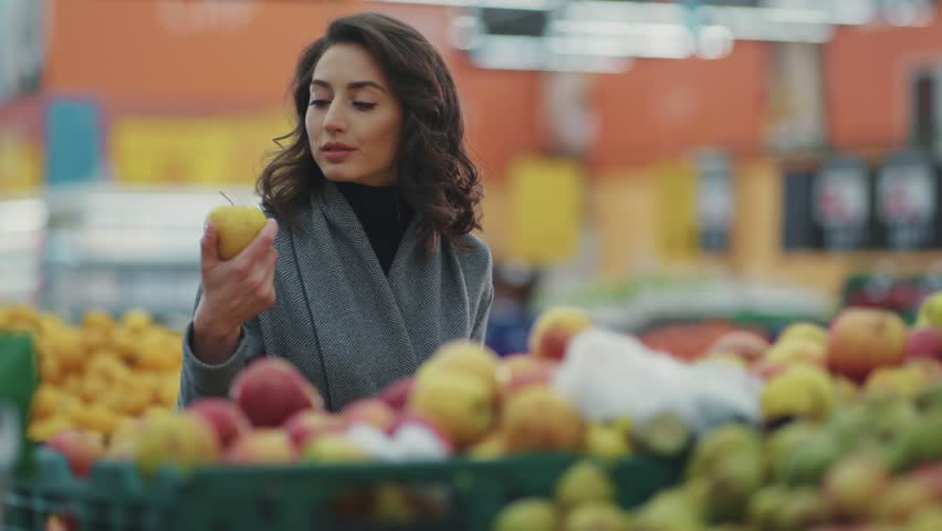 Attractive young woman choosing apple at fruit vegetable supermarket marketplace