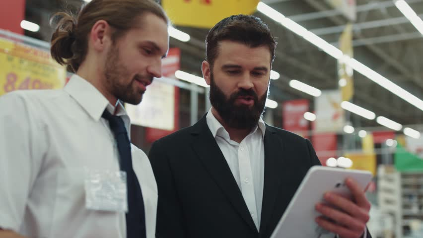 Handsome seller consultant talk with young beard man use hold touch tablet computer in tech store
