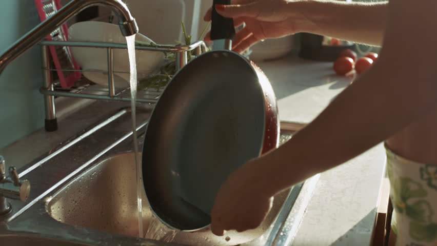 Closeup woman with red manicure rinses frying pan under tap against bright sunlight through window   Shutterstock HD Video #1008730157