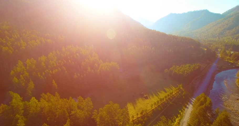 Aerial UHD 4K view. Mid-air flight over fresh mountain river and meadow at sunny summer morning. Green trees and sun rays on horizon. Rural dirt road below. #1008733439