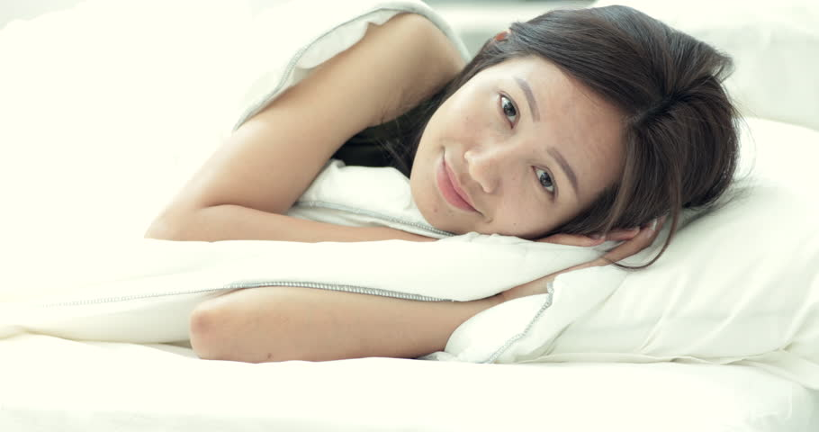 Young beautiful woman sleeping on bed in bedroom And looking camera with smile face . | Shutterstock HD Video #1008735104
