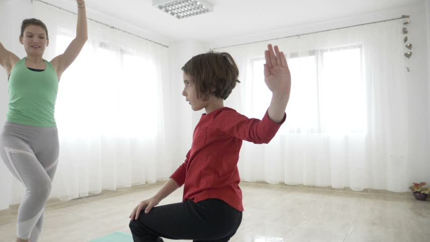Beautiful fit female instructor teaching a little girl standing still yoga poses in slow motion in a bright gym studio #1008745112