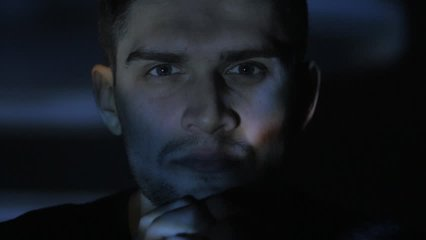 Close up portrait of a young man watching a video or film on TV or a computer monitor. Reflection on his face