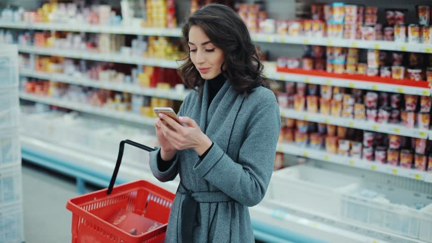 Brunette young woman walk checking to do list on phone in supermarket smiling thinking shopping internet buy technology hypermarket shop mall smartphone grocery market girl food customer slow motion | Shutterstock HD Video #1008755252