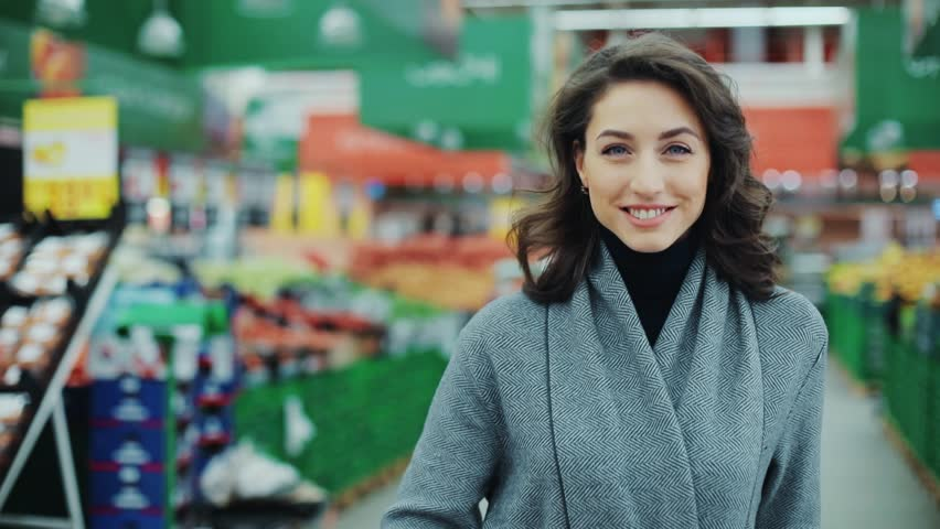 Portrait young woman stands look at camera and smiles while in a produce section in supermarket feel happy girl shopping face retail store pretty customer happiness casual market food consumer | Shutterstock HD Video #1008755273