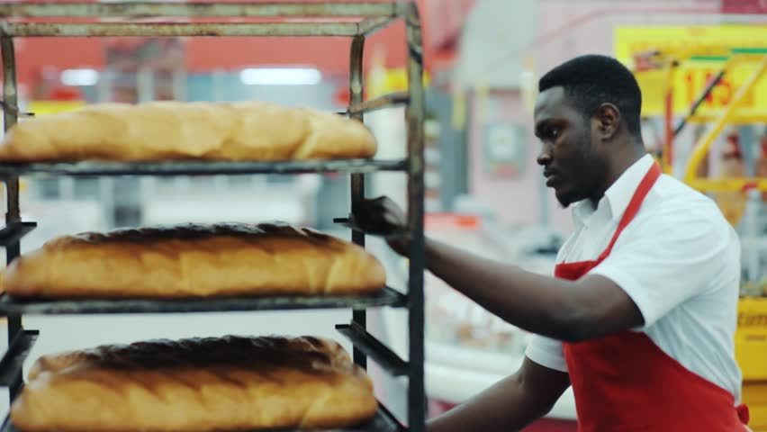 Attractive handsome young african american man seller puts the bread on the counter in supermarket eating job occupation retail work baguette basket staff baker slow motion