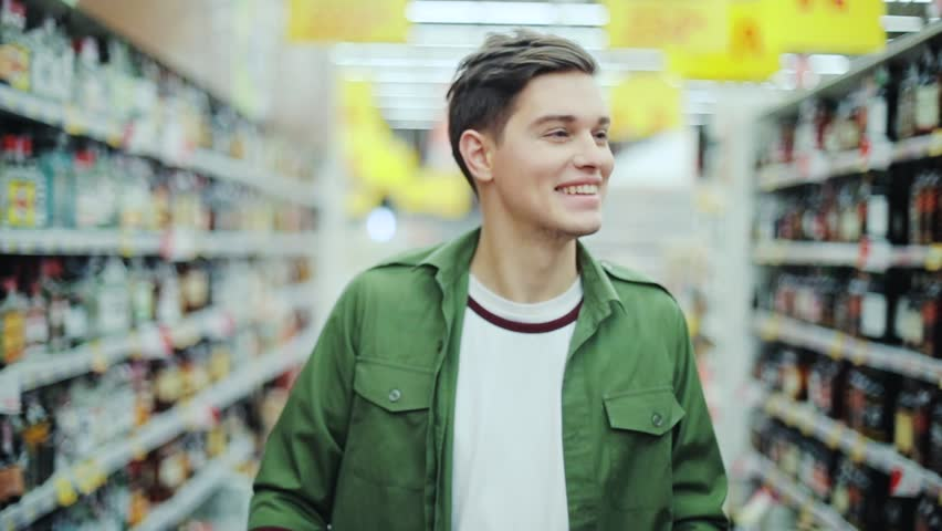 Attractive man walk with shopping cart at the supermarket happy hypermarket hand food shop store customer grocery handsome indoor lifestyle male market buyer guy product shopper slow motion smile | Shutterstock HD Video #1008755291