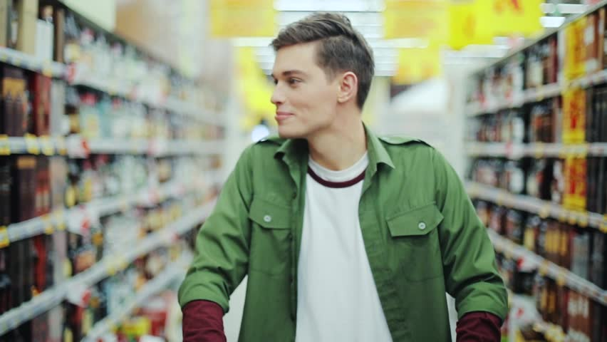 Young smiling man walk with shopping cart at the supermarket feel happy hypermarket hand food shop store customer grocery handsome indoor lifestyle male market buyer guy product shopper slow motion | Shutterstock HD Video #1008755294