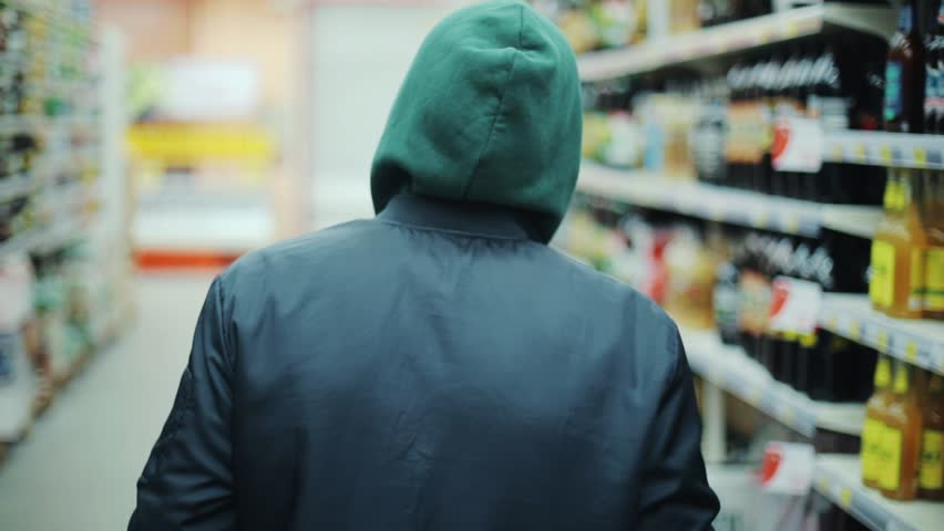 Portrait man steals bottle of alcohol in supermarket go away shot behind shoplifting larceny technology crime store theft criminal customer illegal retail poor looting lifting security shop consumer