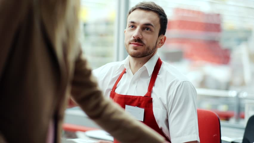 Close up attractive man the seller smiling at the cash register counts the customer in supermarkert shopper cellular copy lady casual mall fashion business hand food fruit store supermarket shop