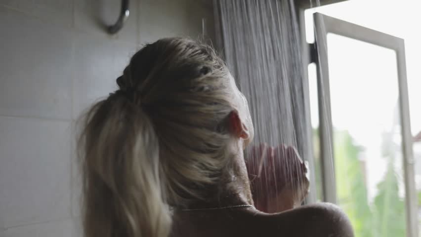 Closeup blond attractive woman or girl refreshing her body in the shower, looking at the opened window, relaxing   Shutterstock HD Video #1008764675