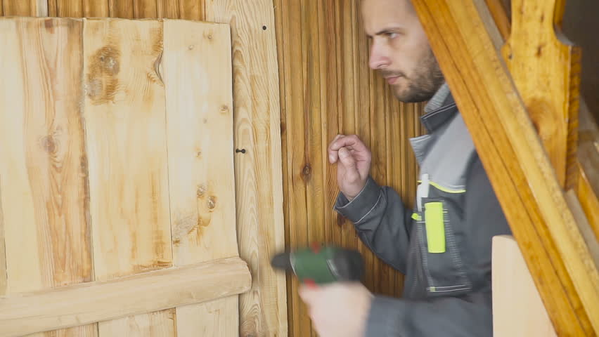 The worker sets up a self-made door in a wooden interior | Shutterstock HD Video #1008768161