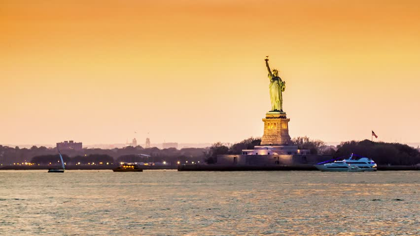 Timelapse with the Statue of Liberty in transition from sunset to night observed from Brooklyn, New York City. Boats criss-cross the Hudson River (4k) | Shutterstock HD Video #10087742
