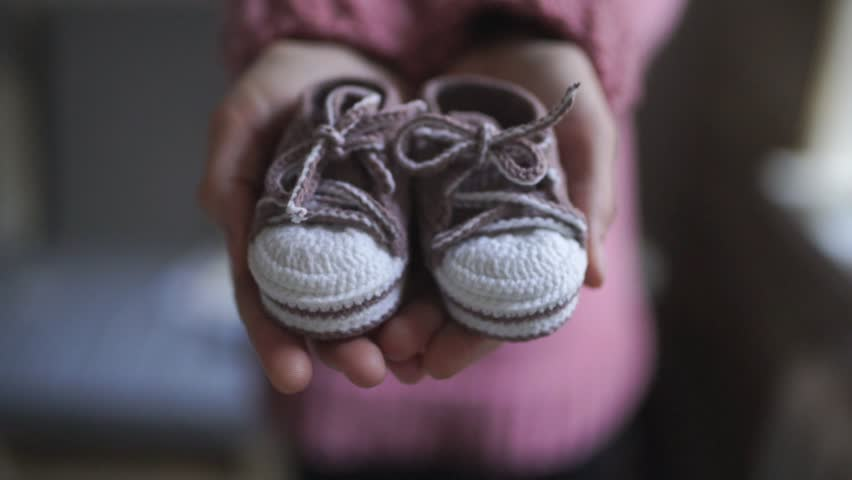 Female hands showing baby booties. Close up handmade baby booties for newborn girl in mother hands. Knitted shoes for children. Pregnancy concept