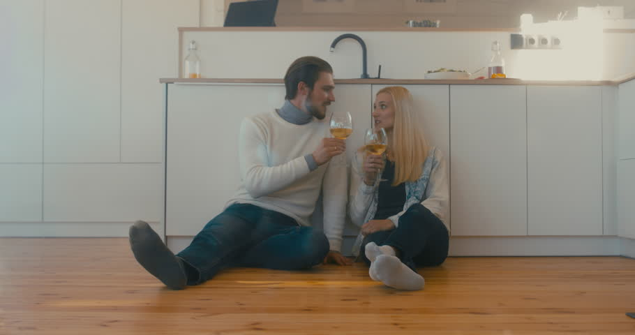 Young adult beautiful Caucasian couple celebrating something at home, drinking wine on the floor. 4K UHD | Shutterstock HD Video #1008781841