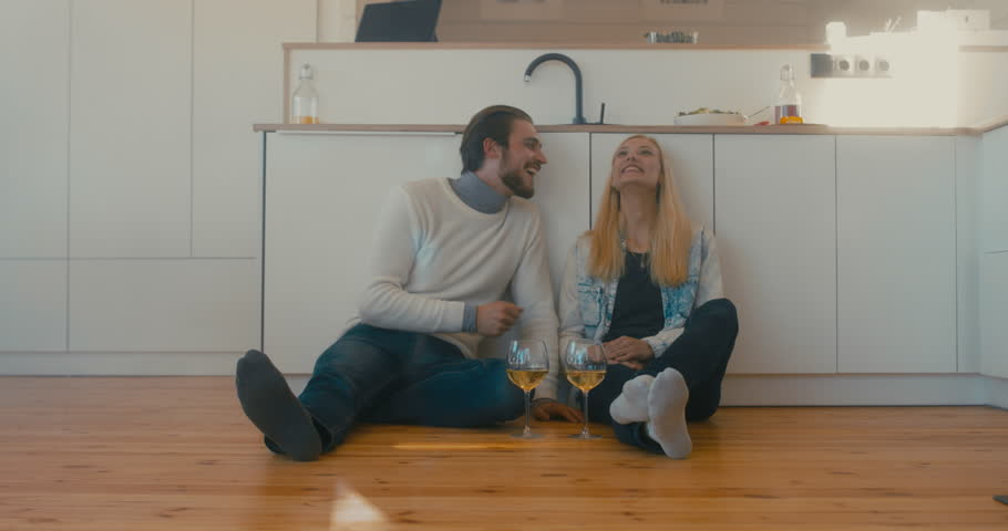 Young adult beautiful Caucasian couple celebrating something at home, drinking wine on the floor. 4K UHD | Shutterstock HD Video #1008781844