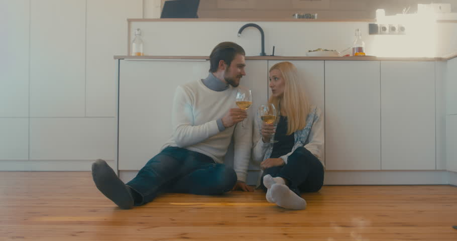 Young adult beautiful Caucasian couple celebrating something at home, drinking wine on the floor. 4K UHD | Shutterstock HD Video #1008781850
