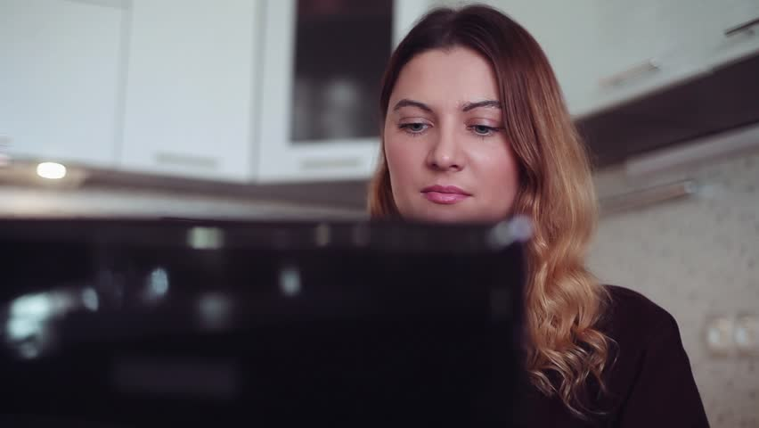 Close-up. Beautiful young girl with good mood typing on laptop. Home style. | Shutterstock HD Video #1008798128