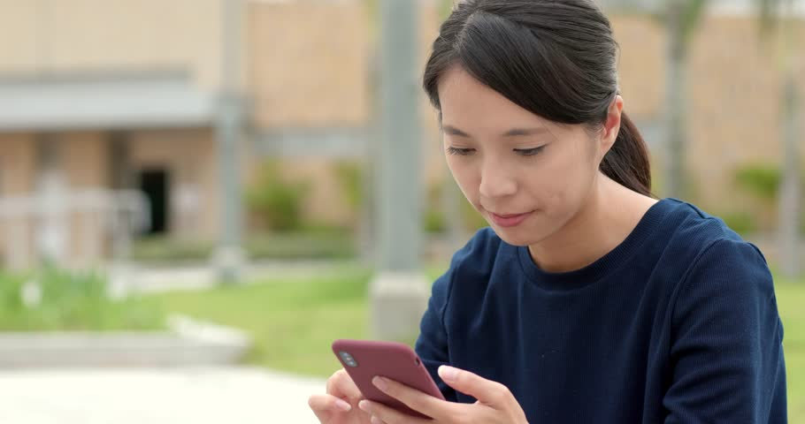 Woman use of smart phone at park   Shutterstock HD Video #1008802538