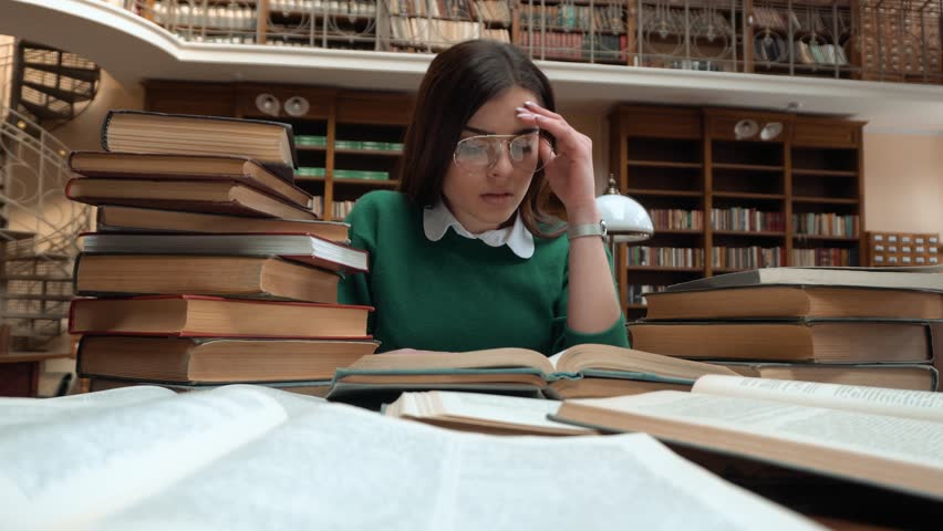 Intellectual girl got tired as reading in library, female student in green sweater and fashionable glasses doing research, indoor shot at the table full of books | Shutterstock HD Video #1008806525