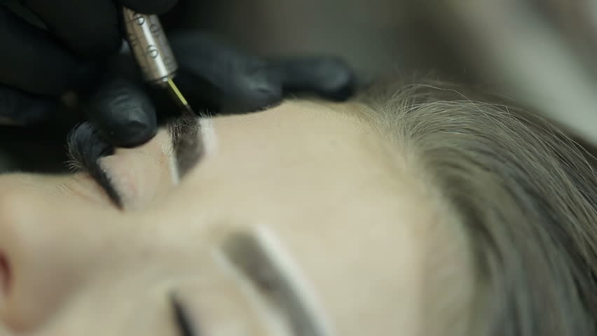 Close up of cosmetologist making microblading procedure.