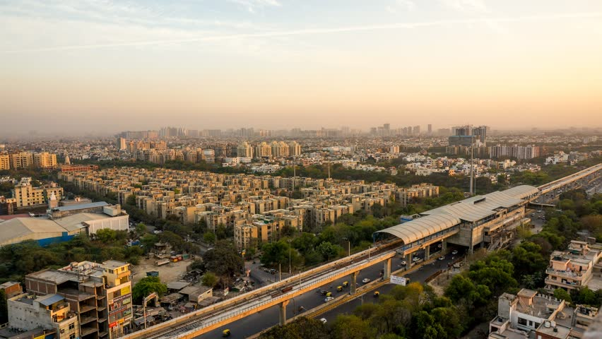 aerial timelapse shot of delhi noida gurgaon cityscape from evening to night shot over an hour with the sun setting, dusk light and the building lights coming on. Shows an incomplete metro station Royalty-Free Stock Footage #1008808064
