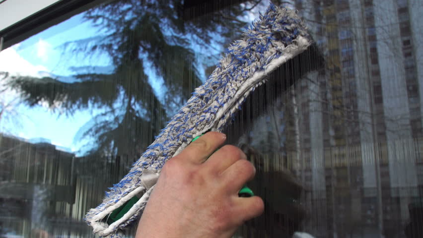 Cleaning the window. A young man cleans and polishes windows with a sponge Royalty-Free Stock Footage #1008810788