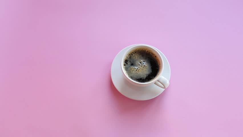 Hand puts coffe on table. Top view, pink background. Stirring coffee. Royalty-Free Stock Footage #1008816629